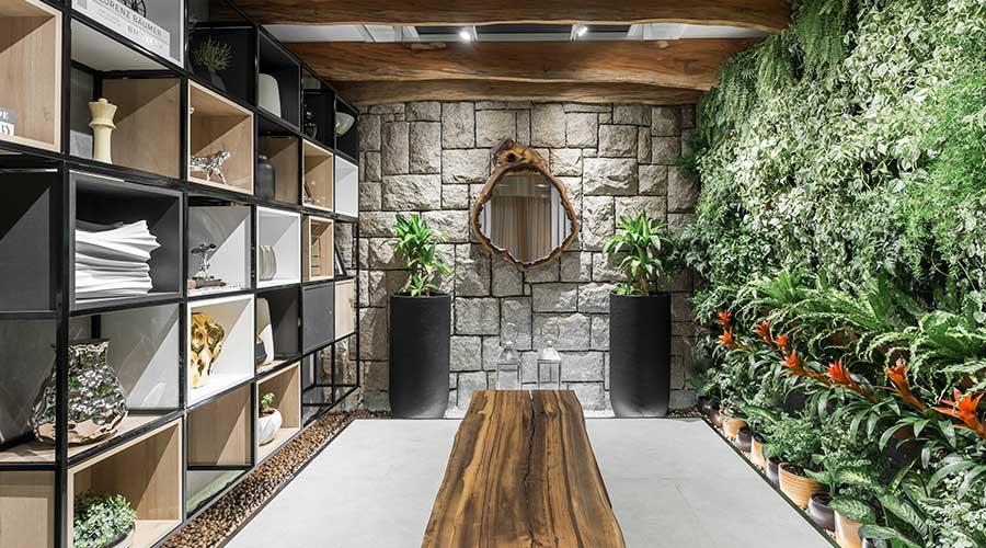 No Jardim de Inverno da Casacor PR, nichos organizadores com o padrão Riviera combinam com a naturalidade da parede de pedra e o jardim vertical